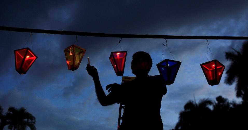 8.set.2016 - Homem acende velas durante o Festival das Lanternas na véspera das com comemorações do nascimento da Virgem Maria em Ahuachapan, em El Salvador