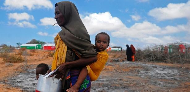Mãe com dois filhos anda até um centro de distribuição de comida na Somália, o país enfrenta sua terceira fome em 25 anos