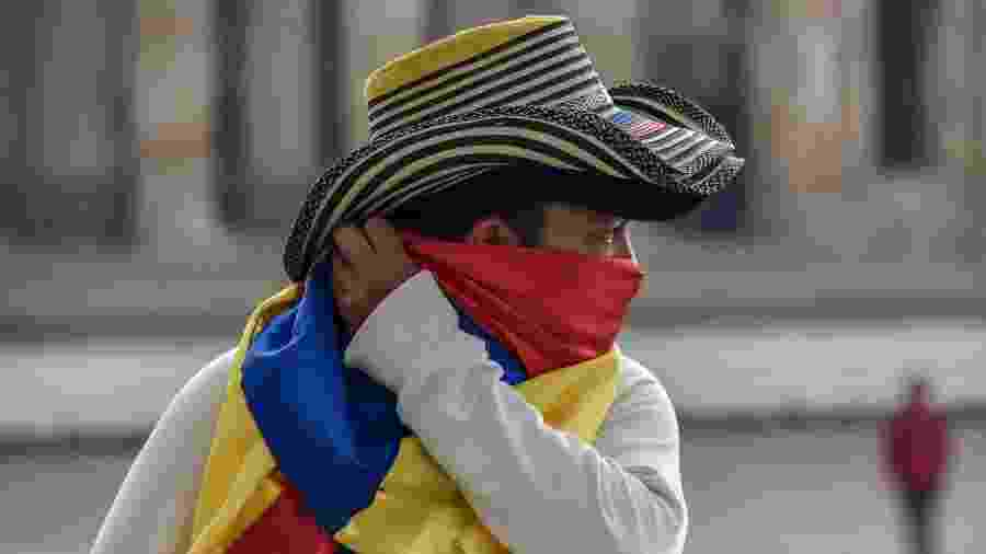 Homem protege o rosto na Colômbia durante a pandemia do novo coronavírus - Guillermo Legaria Schweizer/Getty Images