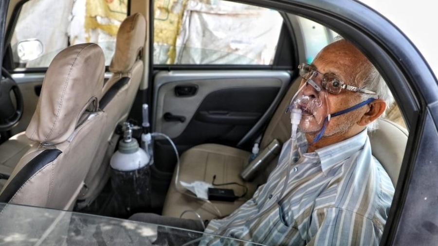 Sushil Kumar Srivastava foi fotografado sentado em seu carro, amarrado a um cilindro de oxigênio na cidade de Lucknow - Sumit Kumar