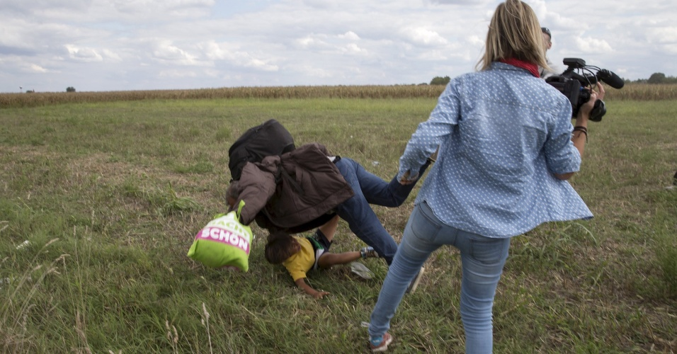 8.set.2015 - Migrante carregando uma criança cai após tropeçar na cinegrafista (Dir.) Petra Laszlo ao tentar escapar de um ponto de fiscalização na vila Röszke, na Hungria