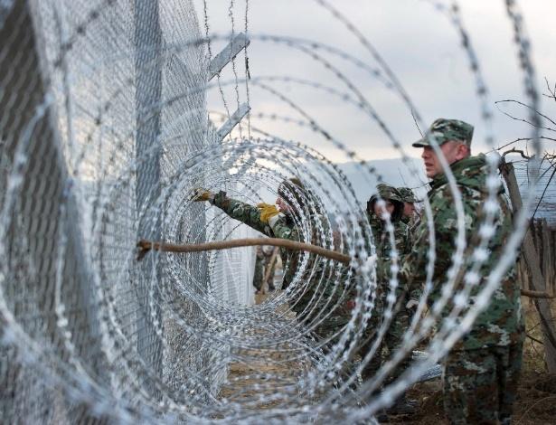 8.fev.2016 - Soldados do Exército da Macedônia trabalham na instalação de uma segunda barreira para conter a passagem de imigrantes considerados ilegais por seu território, na fronteira com a Grécia, perto da cidade de Gevgelija