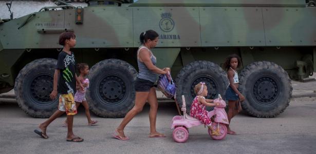 Mulher e crianças passam por veículo das Forças Armadas na Vila Kennedy, no Rio - Mauro Pimentel - 7.mar.2018/AFP