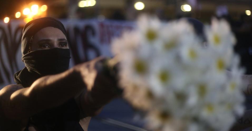 20.mar.2018 - Para pedir o fim da violência, manifestante carrega um buquê de flores brancas durante ato na Candelária, no centro do Rio de Janeiro, que marca o sétimo dia da morte da vereadora Marielle Franco (PSOL-RJ) e do seu motorista Anderson Gomes
