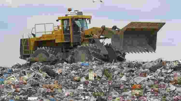 Trator circula sobre montanha de lixo  - Shutterstock