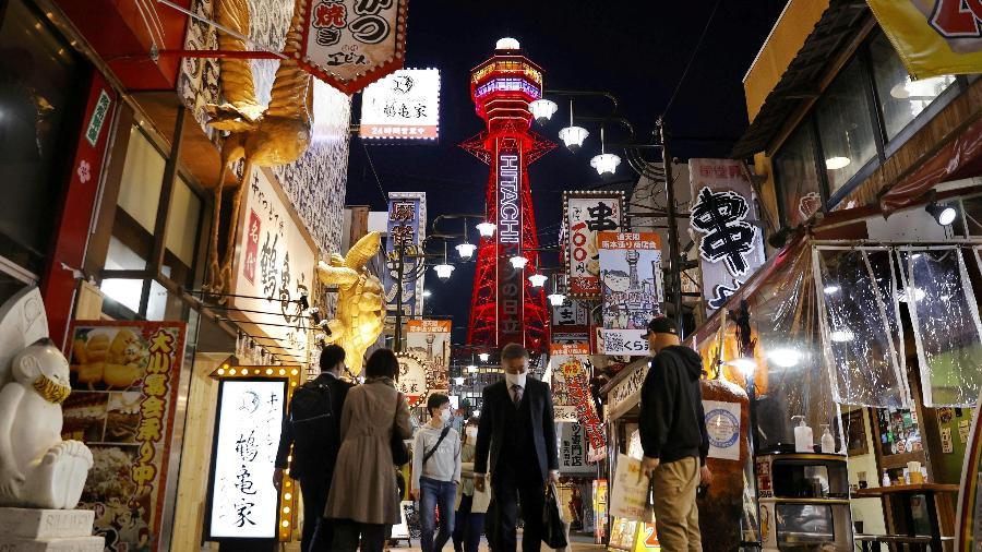7.abr.2021 - Pedestres usando máscaras de proteção contra a covid são vistos em frente à Torre Tsutenkaku em Osaka, no Japão - Kyodo via Reuters