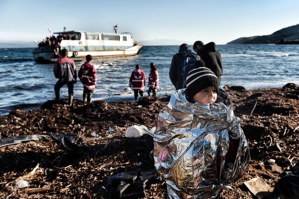 27.out.2015 - Uma criança é embrulhada em cobertor térmico após ser retirado de barco com refugiados que chegou à costa da ilha grega de Lesbos, vindo da Turquia. Mesmo com o clima adverso no mar Egeu devido à aproximação do inverno na Europa, a última semana registrou recorde de chegada de imigrantes, com cerca de 48 mil desembarques, segundo a Organização Internacional para as Migrações