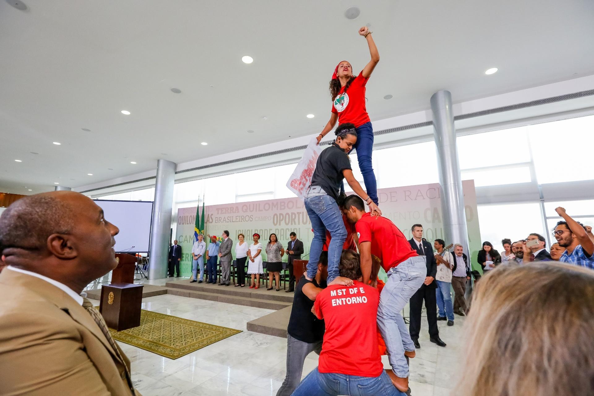1º.abr.2016 - Integrantes do MST apoiam a presidente Dilma Rousseff com uma pirâmide humana antes de cerimônia de assinatura de Atos para a Reforma Agrária e Comunidades Quilombolas