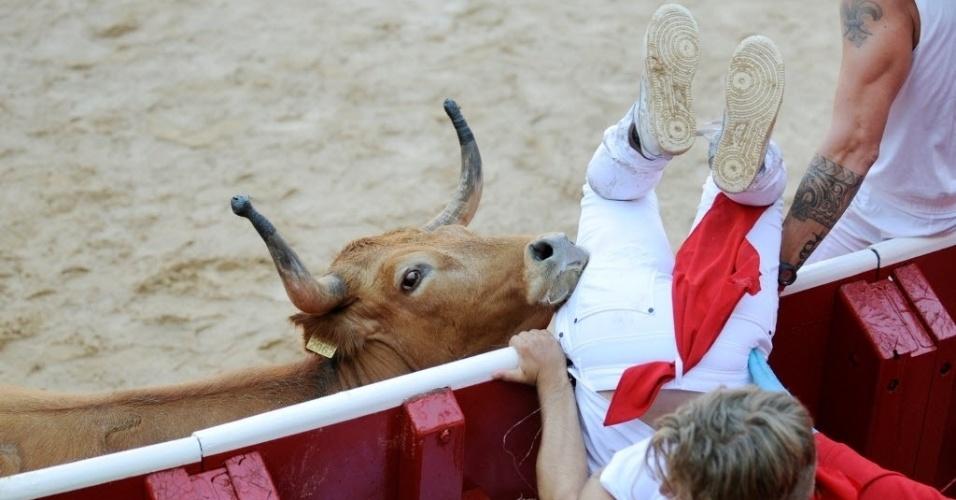 7.jul.2016 - Um folião se joga em área protegida para fugir de touro durante a primeira corrida no festival de São Firmino, em Pamplona, na Espanha