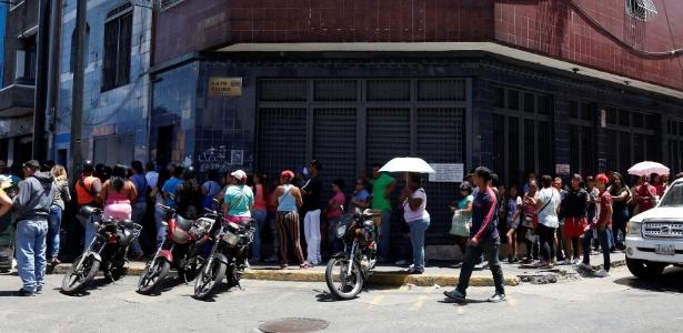 Venezuelanos esperam na fila para comprar alimentos básicos em um supermercado em Caracas