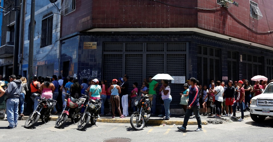 13.jul.2016 - Venezuelanos esperam na fila para comprar alimentos básicos em um supermercado em Caracas. O país com as maiores reservas de petróleo do mundo sofre uma grave crise pela queda dos preços do petróleo, sofre uma forte escassez de alimentos básicos e remédios, além de uma inflação de 180% em 2015. A projeção para 2016 do FMI (Fundo Monetário Internacional) é que chegue a 720%