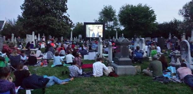 Público assiste a filme em telão em meio a lápides de cemitério dos EUA