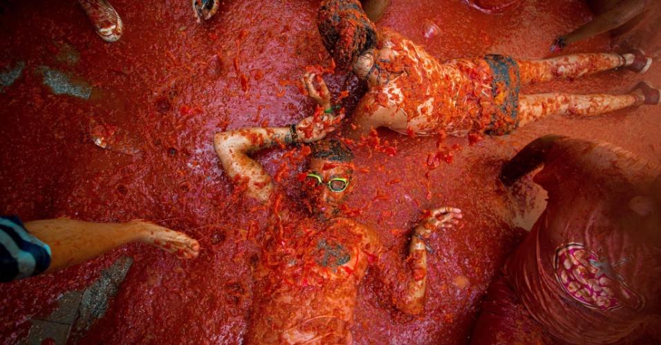31.ago.2016 - Participantes se divertem no chão durante a Tomatina, em Buñol, Espanha