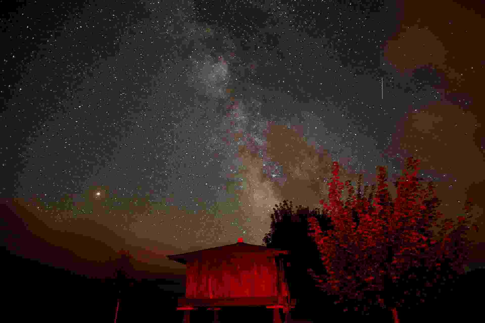 Meteoro entrando na atmosfera terrestre deixa rastro no céu noturno em Berducedo, na Espanha.  As partículas de poeira do cometa Swift-Tuttle entram em combustão ao atravessar atmosfera terrestre, formando a chuva de meteoros Perseidas - Paul Hanna/Reuters