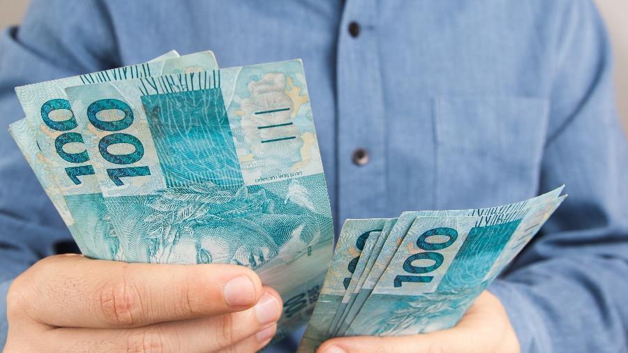 Homem segura dinheiro, investimento, investidor, aplicação, poupança - Getty Images/iStockphoto/Vergani_Fotografia