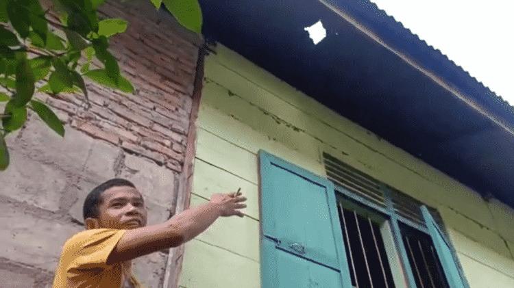 Josua mostra buraco feito por meteorito no telhado da casa - Reprodução/YouTube/Dedi Herianto - Reprodução/YouTube/Dedi Herianto