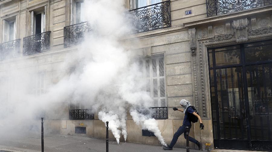 24.jul.2021 - Manifestante atravessa gás lacrimogêneo durante manifestação contra a vacinação obrigatória de alguns trabalhadores, em Paris - Sameer Al-Doumy/AFP
