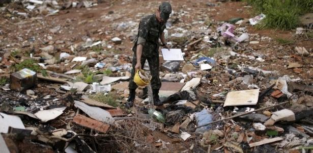 Soldado brasileiro no combate ao Aedes aegypti remove água parada em terreno abandonado em Brasília