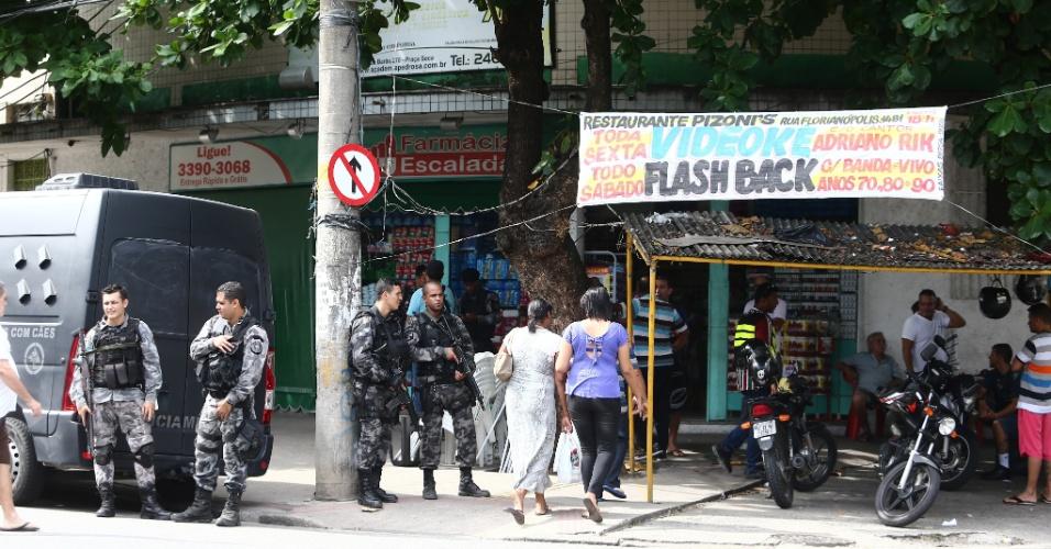 28.mai.2016 - Policiais militares aguardam na região do morro da Barão, em Jacarepaguá, na zona oeste do Rio, onde uma operação policial neste sábado deteve um suspeito de ter participado do estupro coletivo de uma jovem de 16 anos