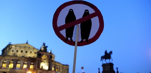 """Integrante do grupo """"Europeus Patriotas Contra a Islamização do Ocidente"""" segura placa contra mulheres com véu em protesto em Dresden, Alemanha"""