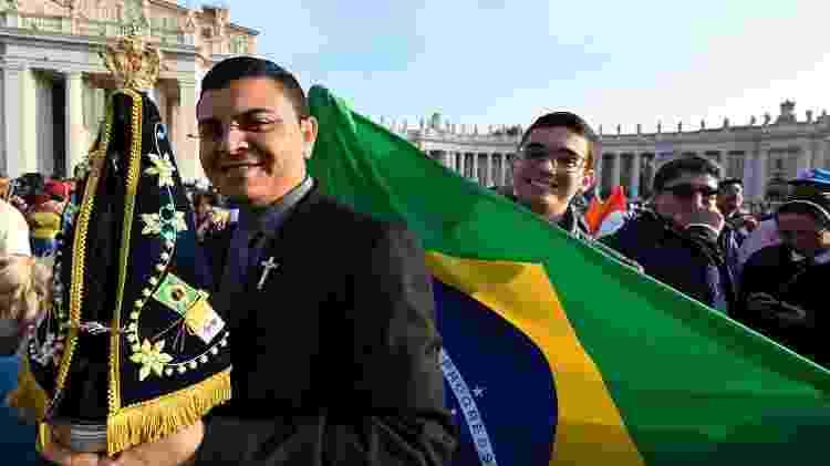 13.out.2019 - Fiéis na praça São Pedro, no Vaticano, durante missa de canonização de Irmã Dulce, com uma imagem de Nossa Senhora de Aparecida e a bandeira brasileira - ALBERTO PIZZOLI / AFP