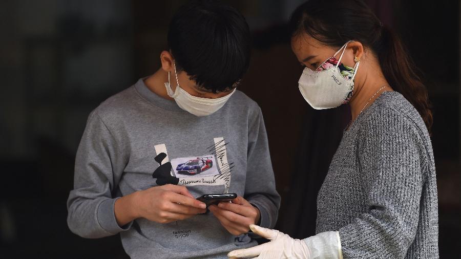 Jovens usando máscaras e luvas para evitar a transmissão do coronavírus checam seus celulares em uma área em quarentena no Vietnã - Minh Nguyen - 13.fev.2020/AFP