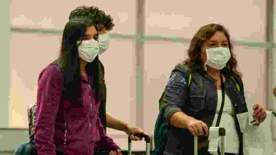 Coronavírus: Passageiros usando mascaras respiratorias são vistos durante desembarque no aeroporto internacional Tom Jobim (Galeao) - Allan Carvalho/Agif/Estadão Conteúdo