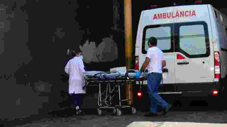 Profissionais de saúde carregam maca em frente a ambulância no Hospital Municipal Salgado Filho, no Rio de Janeiro - Marcos Vidal/Futura Press/Estadão Conteúdo