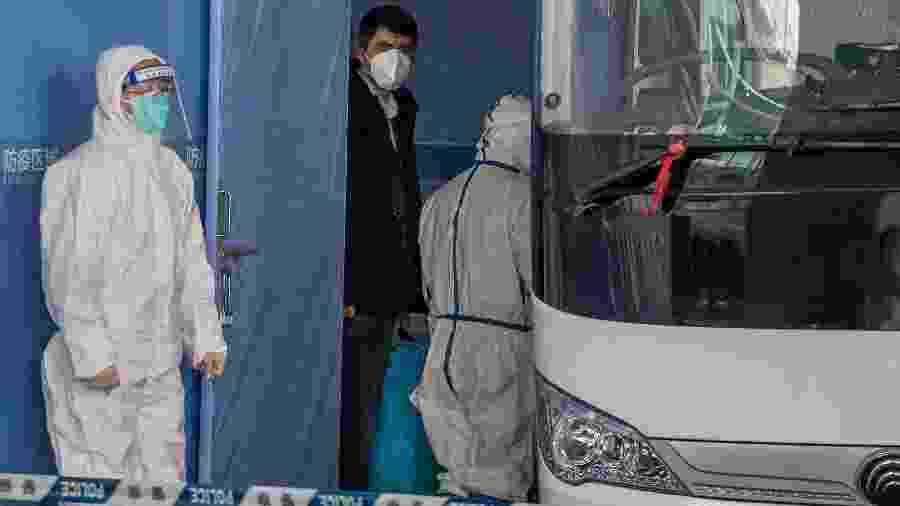 Investigador da OMS (de jaqueta preta) enviado à China para apurar a origem do coronavírus embarca em um ônibus acompanhado de especialistas chineses (com roupas de proteção brancas) - Nicolas ASfouri/AFP