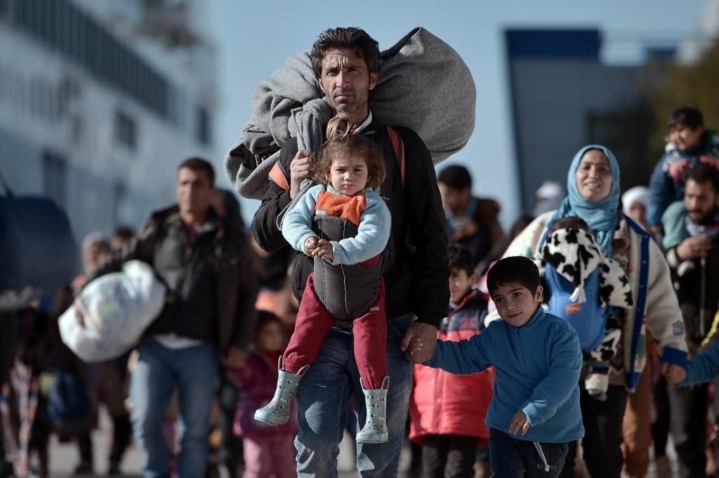 1º.fev.2016 - Milhares de refugiados atravessam a pé o porto de Pireu, na Grécia, depois de chegar ao país pela ilha de Lesbos. Em média, mais de 1.900 refugiados chegam por mês à Grécia em embarcações lotadas, segundo a ONU (Organização das Nações Unidas). A multidão costuma vir, na sua maioria, da Síria, que vive uma guerra civil