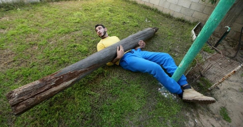 7.mar.2016 - Para demonstrar sua força, Mohammad Baraka, o Sansão de Gaza, deixa um pesado tronco apoiado sobre seu estômago