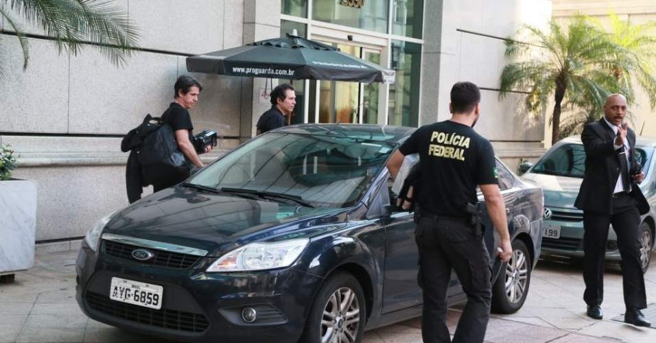 """12.abr.2016 - Equipe da Polícia Federal sai do escritório da construtora OAS, em São Paulo (SP), com pacote. A ação faz parte da 28ª fase da Operação Lava Jato, batizada de """"Vitória de Pirro"""", que investiga a cobrança de propinas para evitar convocação de empreiteiros em comissões parlamentares de inquérito sobre a Petrobras"""