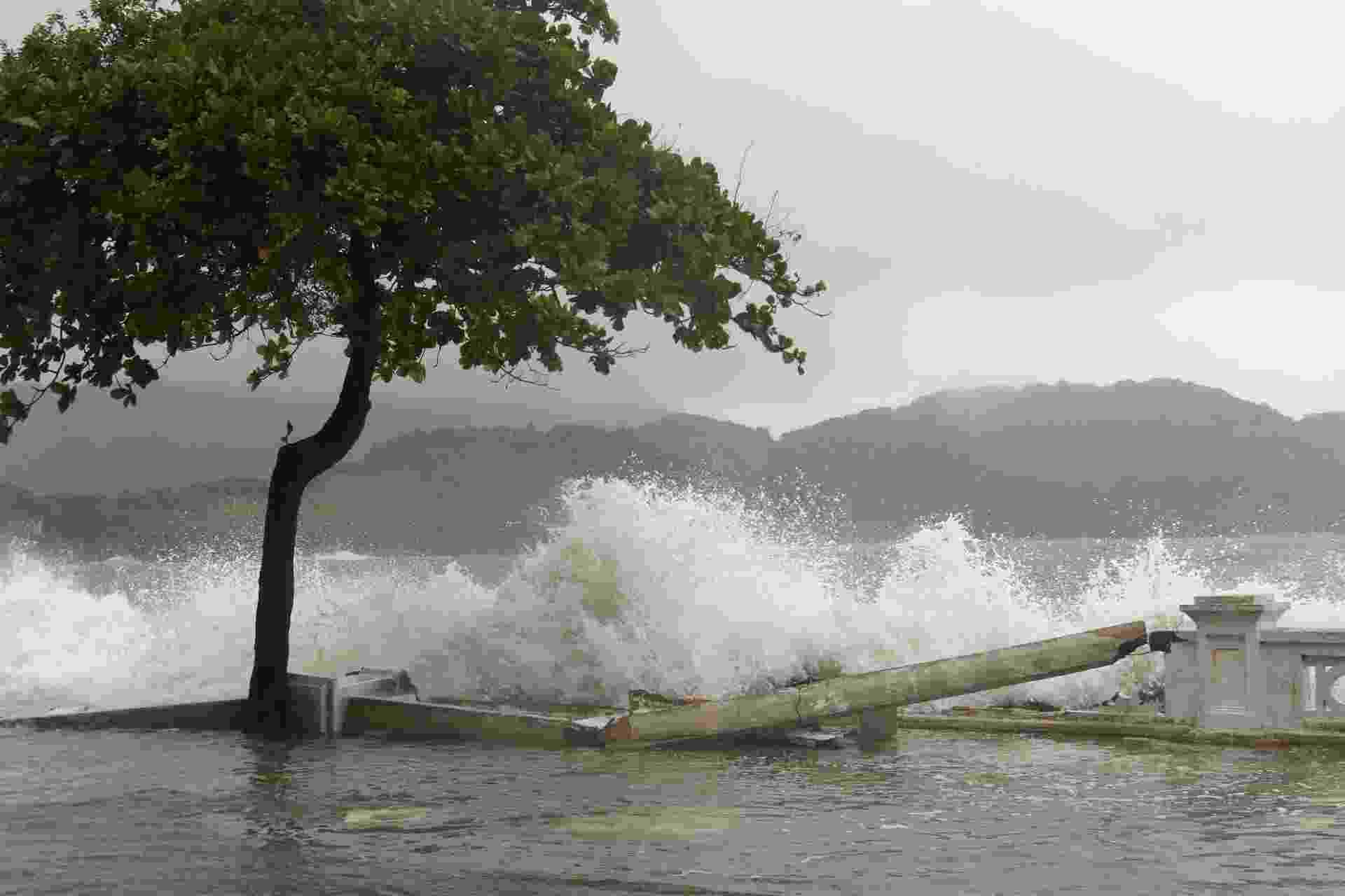 27.abr.2016 - Onda derruba mureta e invade calçadão na Ponta da Praia, em Santos. A frente fria que chegou no Estado de São Paulo provocou ressaca no mar, com ondas de até 3,15 metros, além de chuva e queda das temperaturas. O Porto de Santos precisou ser fechado, e a travessia de balsas foi interrompida - undefined