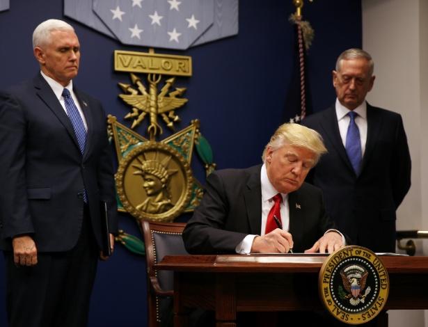 27.jan.2017 - O presidente dos EUA, Donald Trump, assina a ordem executiva revisada que impede a entrada de imigrantes de seis países de maioria muçulmana nos EUA