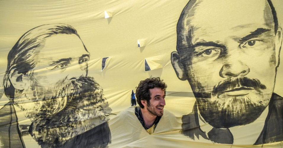 Homem olha através de buraco em bandeira com as imagens do pensador comunista Friedrich Engels (esq.) e do líder soviético Vladimir Ilitch Lenin (dir.) em manifestação do 1º de Maio em Istambul. Esperava-se que os protestos deste ano na capital da Turquia fossem mais moderados, depois de os sindicatos terem dito que não se aproximariam da Praça Taksim, que era o ponto habitual dos grandes protestos no país. Mas houve confrontos entre manifestantes e a polícia e 200 pessoas foram presas