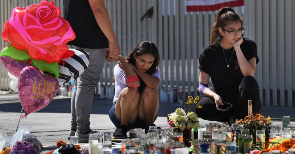 3.out.2017 - Mulheres rezam em um memorial improvisado na avenida Las Vegas Strip, em Las Vegas, em lembrança às vítimas do atentado ocorrido na cidade na segunda-feira (2), quando um atirador matou 59 pessoas e feriu mais de 500