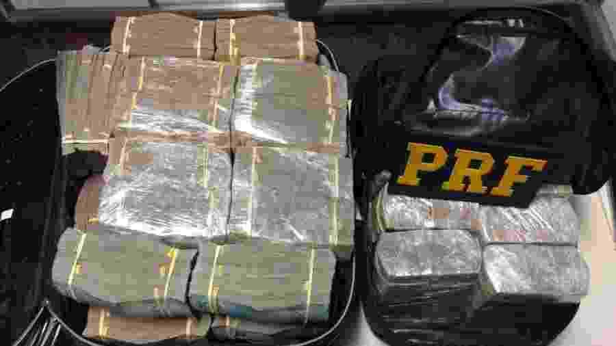 Dinheiro estava embalado em diversos pacotes e dividido em uma mala e uma mochila no bagageiro do carro - Divulgação/PRF-MG