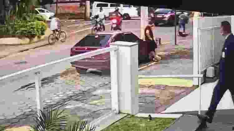 30.mai.2020 - Rafael fica em cima de Ticyana, desmaiada no meio da rua. A cena é observada à distância por um segurança do Hospital Italiano, no Grajaú, zona norte do Rio - Reprodução - Reprodução