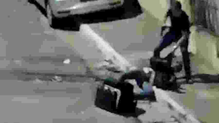 O soldado Felipe, de camiseta escura e armado, arrasta o motoboy André para a calçada - Reprodução