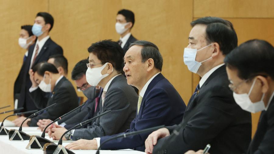 """O primeiro-ministro Yoshihide Suga (ao centro, sem máscara) disse que o governo """"tomará medidas"""" para impedir que isso prejudique a reputação da região - STR/Jiji Press/AFP"""