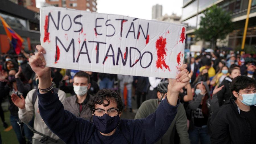 """Manifestante segura placa com os dizeres """"eles estão nos matando"""" durante um protesto contra a pobreza e a violência policial, em Bogotá, Colômbia - Nathalia Angarita/Reuters"""