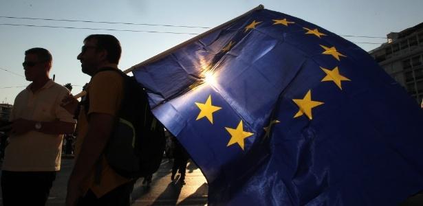 Grupo de manifestantes levam bandeira da União Europeia para frente do edifício do parlamento em Atenas