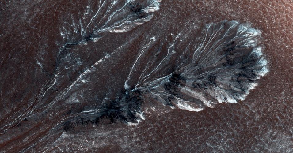 30.jul.2015 - A geada sazonal normalmente acontece em latitudes médias e altas em Marte, muito parecido com a neve do inverno da Terra. No entanto, no planeta vermelho a geada é de dióxido de carbono (gelo seco), em vez de gelo de água. E esta geada parece causar uma reação na superfície, incluindo os fluxos de voçorocas (grandes buracos de erosão). Esta imagem, feita em 11 de abril de 2015, mostra a geada em uma cratera nas planícies do norte do planeta. A geada destaca detalhes da superfície, uma vez que quantidades diferentes de gelo se acumulam