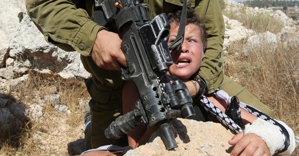 28.ago.2015 - Soldado israelense segura um menino palestino durante confrontos com manifestantes que protestam contra o confisco de terras palestinas, no assentamento judaico Hallamish, na Cisjordânia