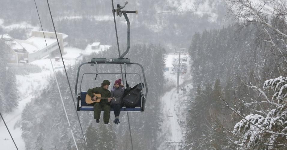 """6.jan.2015 - Mikhail Shakov, 23, toca violão para sua namorada em teleférico de estação de esqui em Krasnoyarsk, na Rússia. Ele integra o clube Cryophile de nadadores de inverno. Para Shakov, nadar no frio é uma forma de se desconectar da rotina estressante. """"Todos os problemas saem de mim"""", diz"""