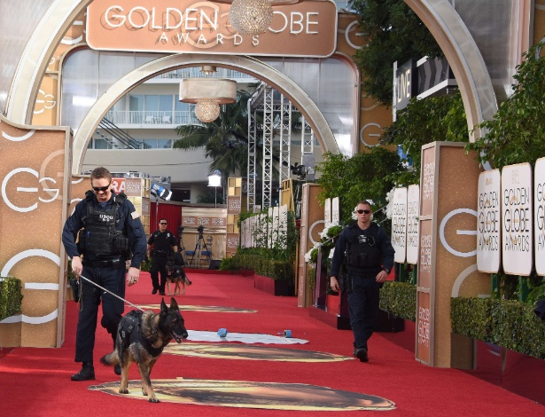 10.jan.2016 - Cão farejador, junto com agente da Guarda Costeira dos EUA, verifica entrada do local onde acontece a premiação do 73º Globo de Ouro, em Beverly Hills, na Califórnia