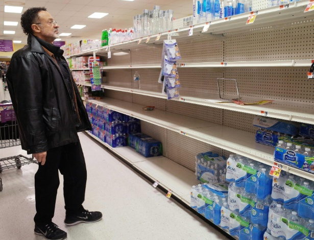 Homem olha prateleiras vazias na seção de água em supermercado de Washington