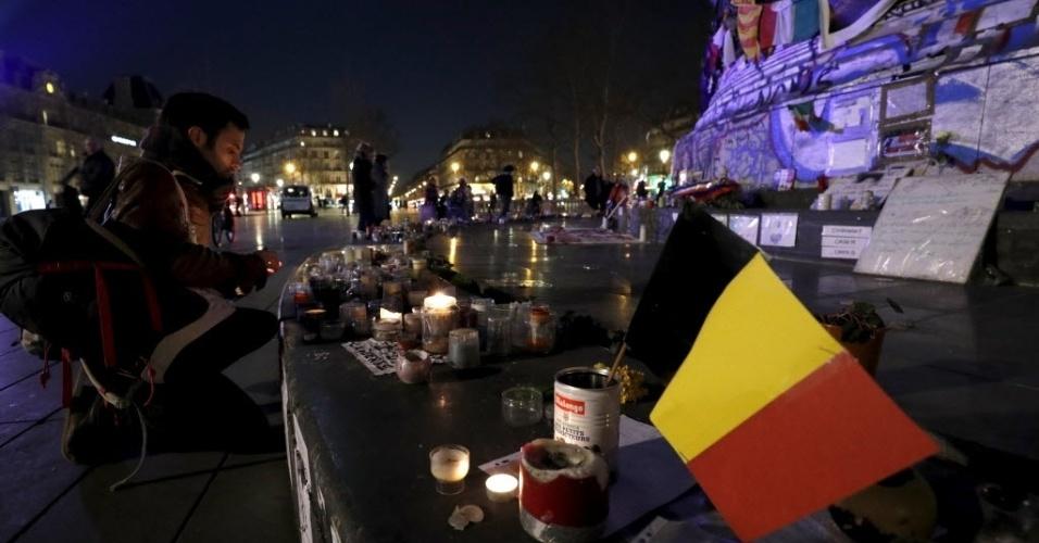 22.mar.2016 - Um parisiense acende uma vela ao lado de bandeira da Bélgica na praça de La Republique, em Paris, na França. O local está sendo usado como palco de homenagem aos mortos no ataque terrorista executado pelo grupo Estado Islâmico nesta terça-feira