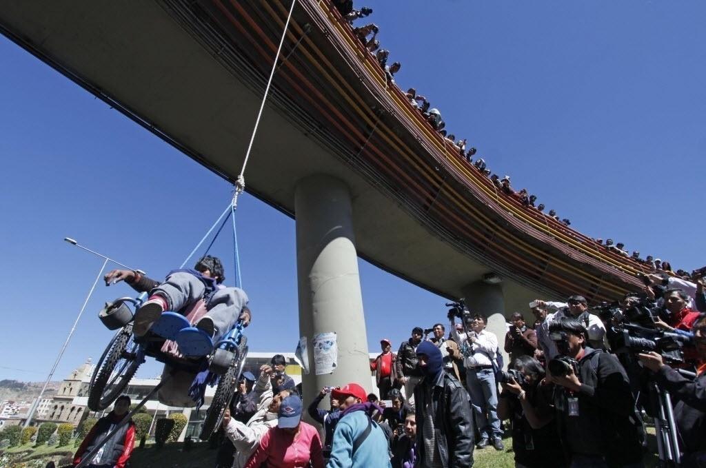 3.mai.2016 - Um homem em uma cadeira de rodas é pendurado em uma ponte durante um protesto de pessoas com deficiências em La Paz, na Bolívia. A manifestação pede que o governo forneça um bônus econômico mensal para ajudar no tratamento dos pacientes