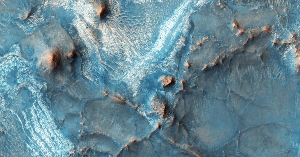 AS CORES DE MARTE - Nili Fossae é a região mais colorida de Marte. Ela é uma fratura na superfície do planeta parcialmente preenchida por sedimentos. As regiões de Marte geralmente são homogêneas por conta do regolito (camada de poeira, solo, rocha quebrada e outros materiais), mas neste local o solo é exposto, exceto quando há dunas de areia